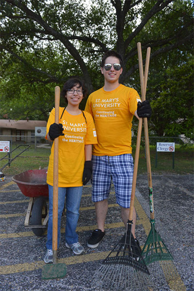 Two students stand proud after doing volunteer yard work.