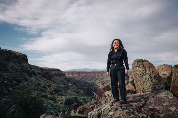 Dr. V in front of a scenic view of canyons in Taos