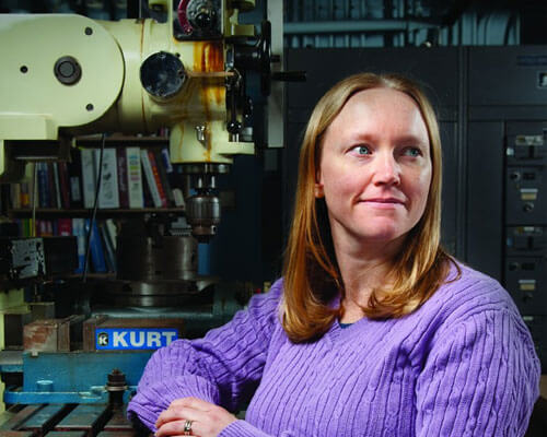 Amber McClung, Ph.D., who teaches Mechanical Engineering, poses with equipment in her lab.