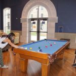 Two students play pool in a Founders Hall first-floor lounge