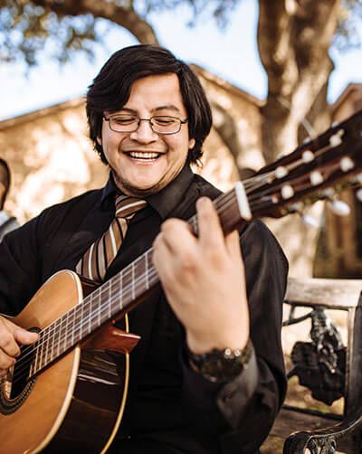 Marianist aspirant Trinidad Agosto plays the guitar in Pecan Grove