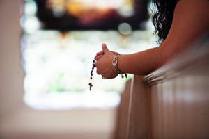 A lady holding prayer beads in a chapel on St. Mary's campus