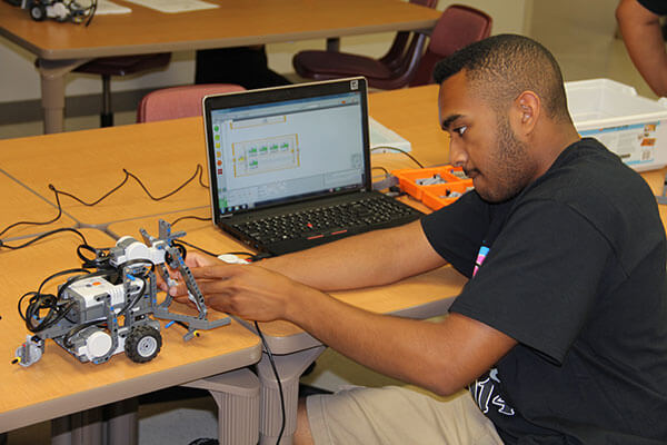 A student connects a robot to his computer at summer robotics camp