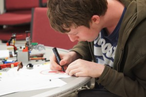 A student works on a drawing of a robot in the S.A. Best competition