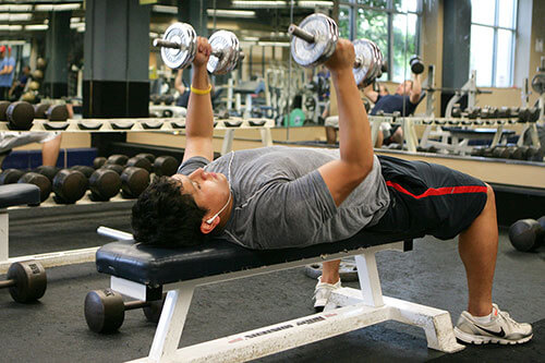 A student lifts weights inside the AA&CC athletic facility
