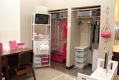 An organized dorm room with shelving, portable drawers and hooks for purses and coats