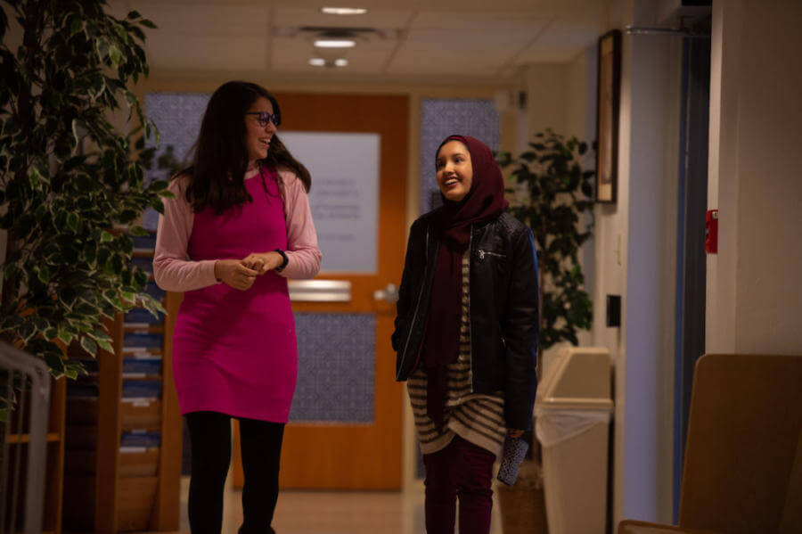 Two students walk through a hallway smiling