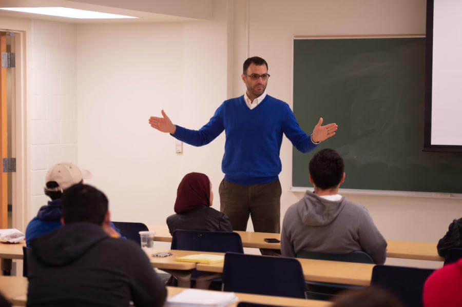 International Studies professor stands in front of a class with his arms spread wide for emphasis