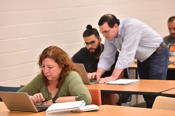 Cyber security student works on a computer. A professor helps another student beside her.