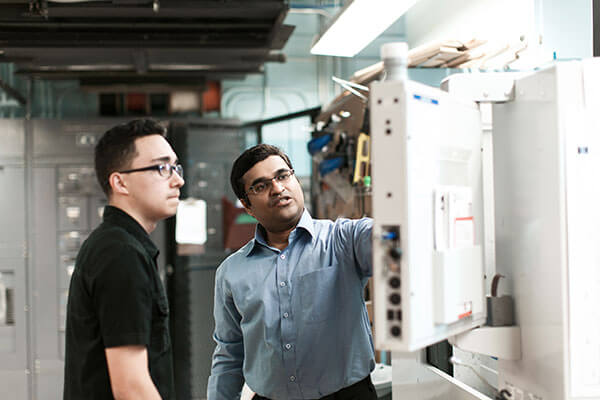 Gopal Easwaran, Ph.D., in the Industrial Engineering lab with a student.