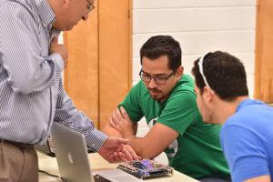 Djaffer Ibaroudene, Ph.D., helps students in class.