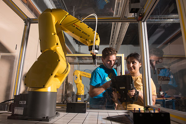 Students operate robotic arm in Industrial Engineering lab.