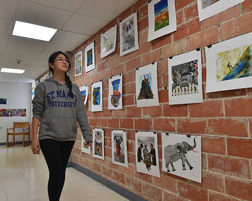 Female student walking alongside art display of student artwork