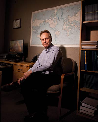 Dr. Johnson in his office in front of a world map