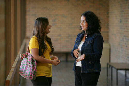 Public administration student speaking with a professor on a library patio