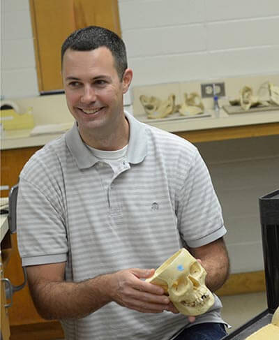 Ted Macrini holding a model of a skull