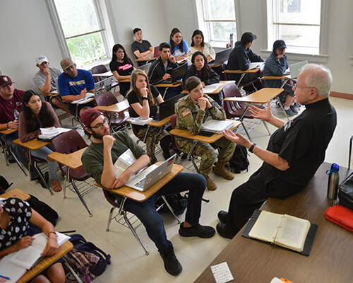 theology professor lecturing to class full of students