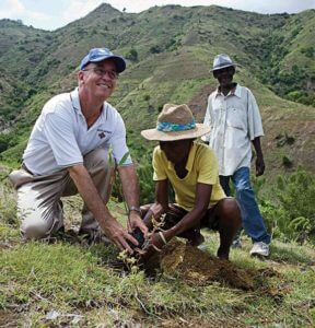 Tom Mengler helps plant a tre in Haiti