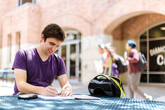 Student does homework in front of the University Center.