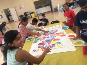 Children finger painting at the Summer of Service Program.