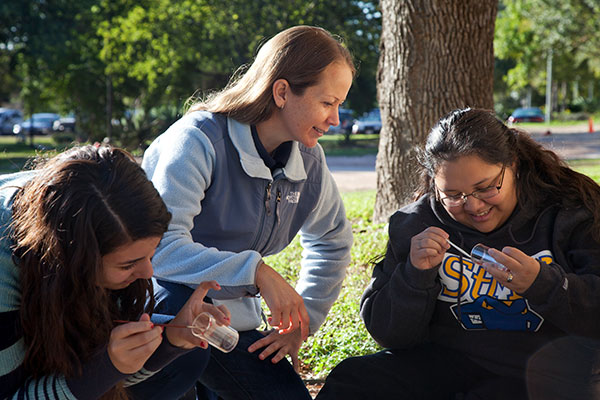 Melissa Karlin, Ph.D., instructs students during an on-campus lab in which they painted and tracked ants.