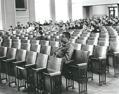 Young Louis Cousins sit alone in auditorium