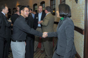 An E-Scholar greets and networks with guests at a Forum on Entrepreneurship Breakfast Series event.