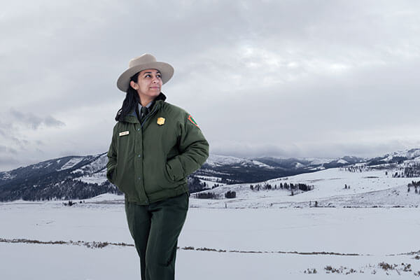 Lianna Duran in her ranger uniform, standing in front of snow-capped mountains
