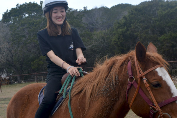 A summer program student rides a horse, a typical Texan adventure