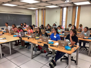 Computer science classroom full of girls learning how to code at summer camp