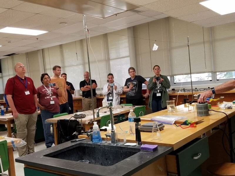 A group of ASM teachers watches an experiment involving paper on a wire