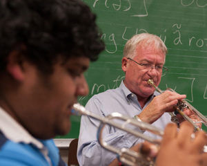 John Rankin and a student play trumpet together in a music classroom