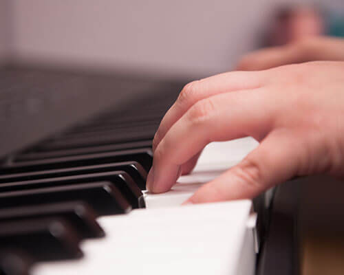 A student's hands on a piano keyboard