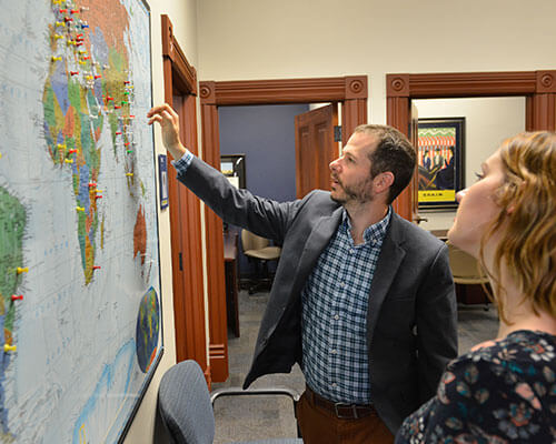 Professor points toward thumbtacks on a world map