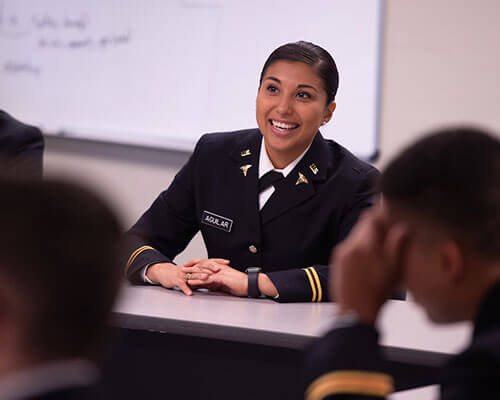 Female ROTC cadet in dress uniform, sitting in front of a whiteboard in a classroom