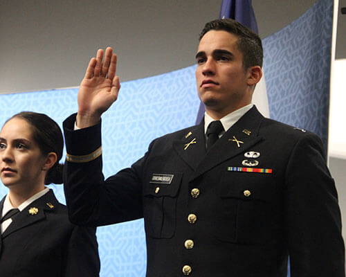 Two cadets in dress uniform salute