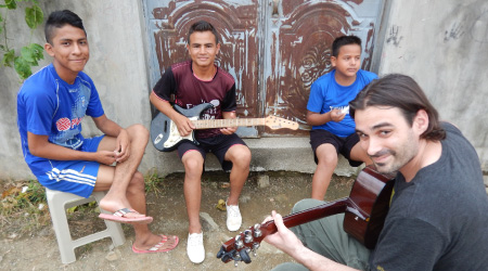 A student plays guitar with three children while studying abroad