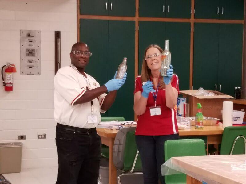 Two ASM teachers hold up bottles while conducting an experiment at summer camp