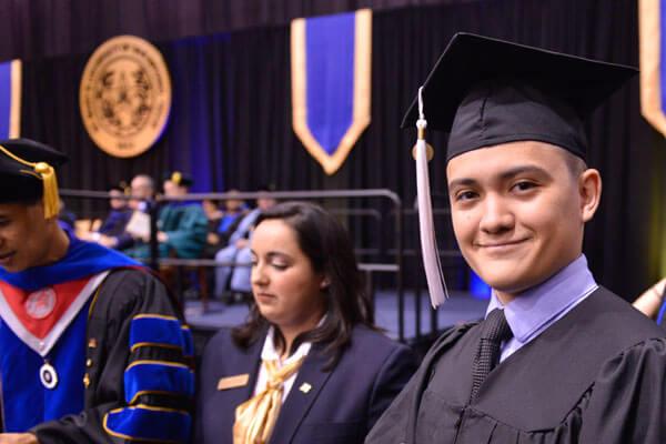 A male student graduates in regalia