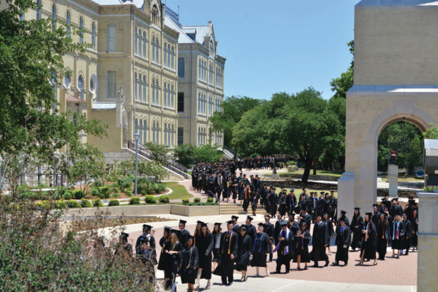 Students in regalia process by the Bell Tower to their commencement.