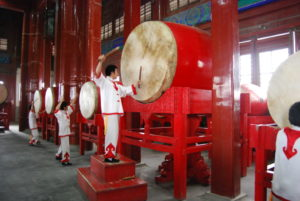 A person beats a big Chinese drum.