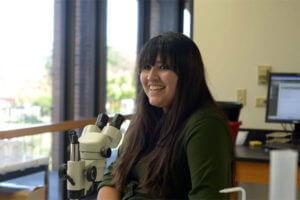 Student stands by microscope.