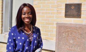 J.D. student Aisha Denis stands in front of St. Louis Hall.