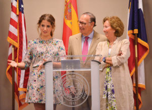 Cayetana Roca de Togores (from left), granddaughter to the Duque de Béjar; Duque de Béjar Pedro Roca de Togores; Duquesa Marta Garcia Perez, stand at a podium.