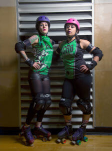 Samantha Franklin and Melanie Call stand in full roller derby gear.