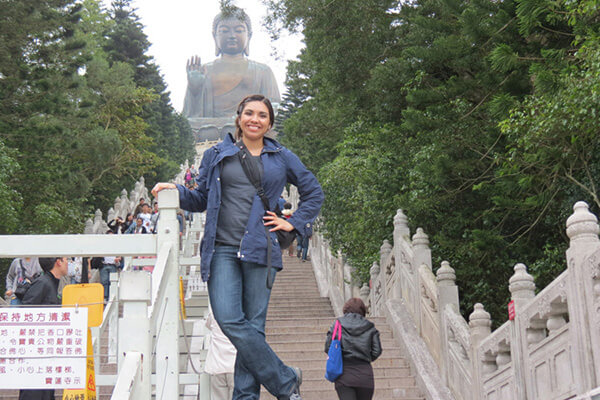 A female student stands at the bottom of a staircase leading to a giant Buddha statue