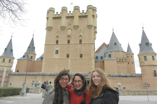 Three students stand in front of a castle in Alcala, Spain