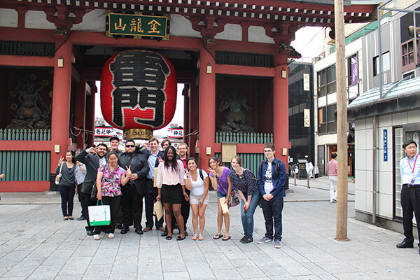 A group of students poses in front of a Chinese building featuring an ornate traditional lantern