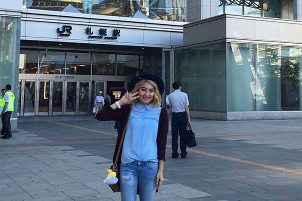 Female student smiles in front of a building with a Japanese logo