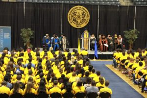 Students in t-shirts listen to academic convocation.